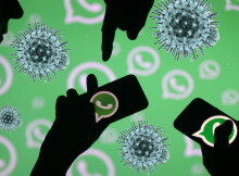 Men pose with smartphones in front of displayed Whatsapp logo